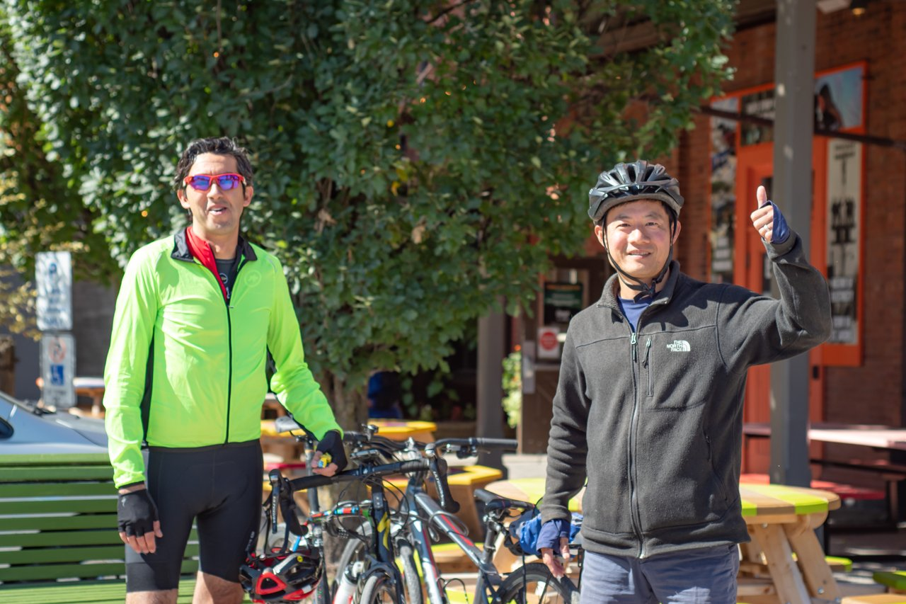 two male cyclists outside the old Flour Mill building in St. Jacobs: one is wearing a helmut, smiling and giving the thumbs up sign. the other is smiling and standing beside his bicycle