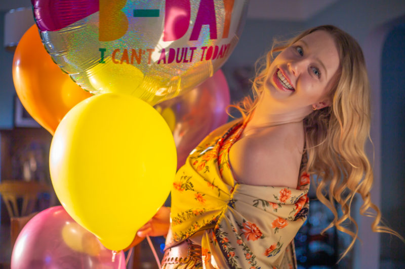 photo of a smiling woman holding on to helium balloons that say Happy Birthday
