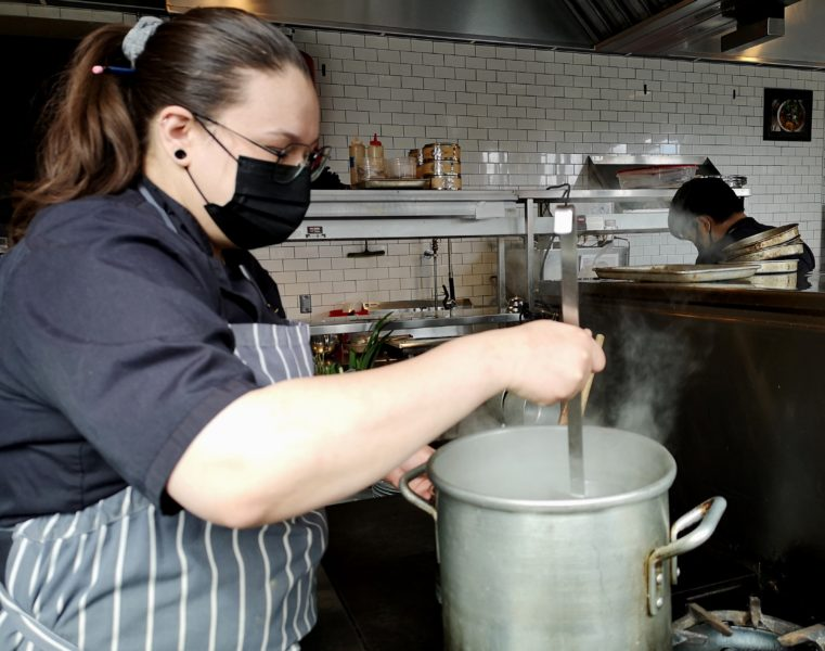 chef Annie Street in the kitchen at Loloan Lobby Bar in Uptown Waterloo, at the stove stirring a steaming pot
