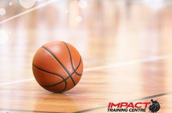A basketball sitting on the floor of an indoor basketball court with the name Impact Training Centre written in the right hand corner of the photo