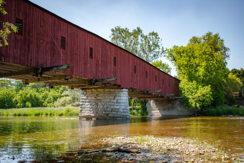 Looking at the outside of the West Montrose Covered Bridge with a view of theGrand River flowing underneath it