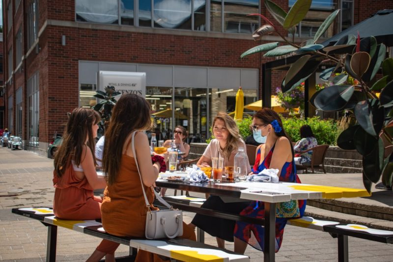 four women sitting at a painted Art Fresco Table Trail picnic table on the patio of The Bauer Kitchen in Waterloo on a sunny summer's day