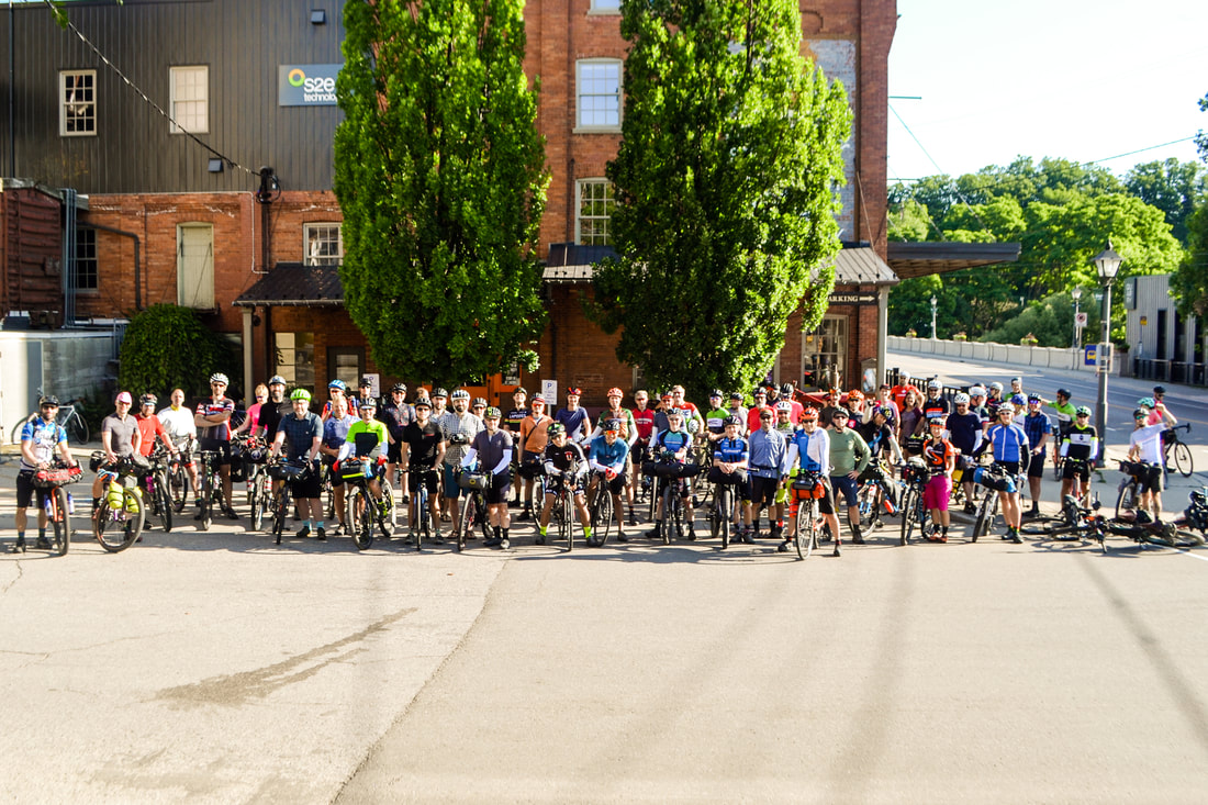 Many cyclists gathered together in front of EcoCafe in St. Jacobs after completing the BT700 Bikepacking route in the summer