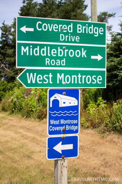 Two green street signs and a blue Provincial sign directing people to the West Montrose Covered Bridge in Woolwich Township