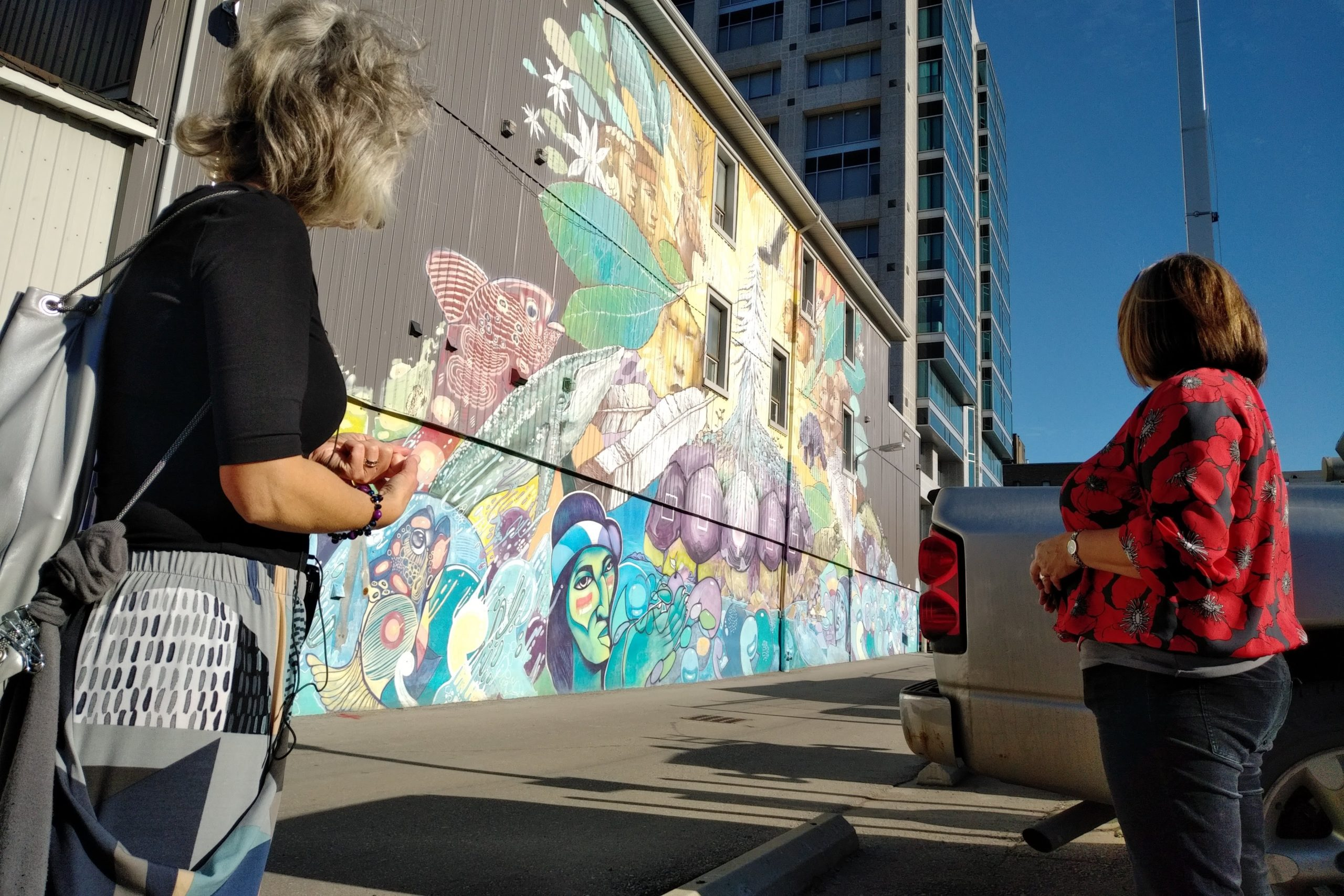 Juanita Metzger of Stroll Walking Tours speaking to a tour guest and explaining a colourful wall mural located in Downtown Kitchener