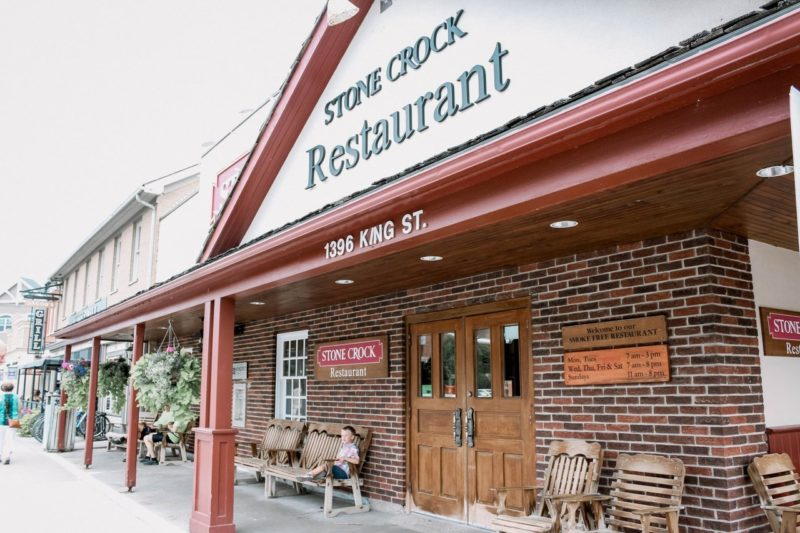 the outside front view of the Stone Crock Restaurant in St. Jacobs with its traditional brick and wood facade and double wooden doors leading into the restaurant