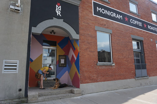 a female and her dog outside the entrance to Monigram Coffee Roasters in Cambridge