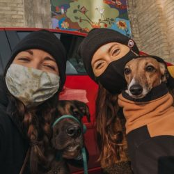 picture of two women in toques and dressed for winter, outdoors and posing with their dogs who are also dressed for winter in front of a wall mural in Waterloo Region