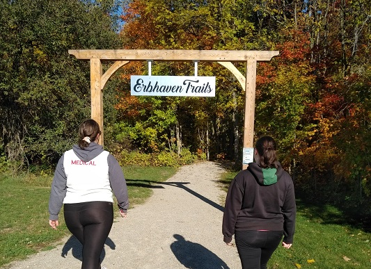 two women walking along the Erbhaven Trail in Wellesley. It's a sunny fall day, and the leaves on the trees along the trail are beginning to change colour