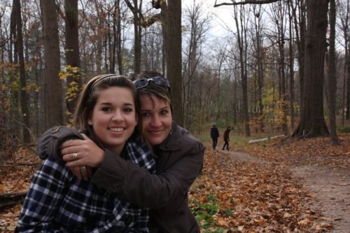 a woman hugging another woman on a trail in a wooded area: there are lots of coloured leaves on the ground, and the women are wearing fall attire