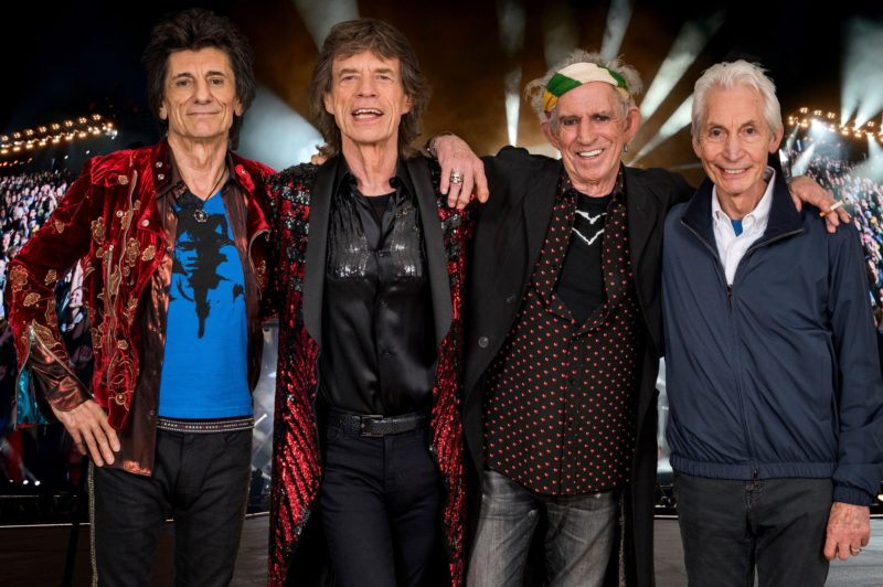 the four embers of The Rolling Stones band standing together with their arms around each other, smiling
