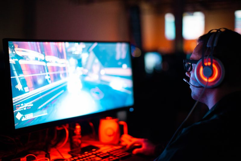 an esport gamer at his computer and involved in a game as part of a tournament: the screen is very bright while the background is dark with low lighting