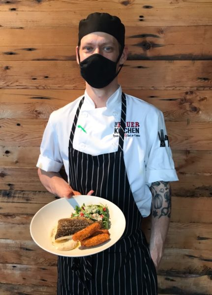 Chef Tyson Murr holding a freshly prepared entre featuring cod. He's standing in front of a wall at The Bauer Kitchen in Uptown Waterloo, and he's wearing a mask.