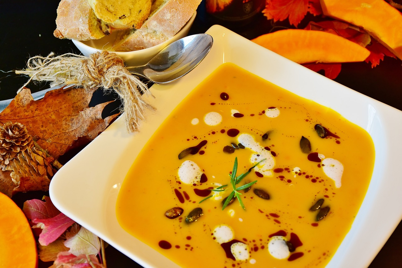 a white bowl of orange pumpkin soup garnished with sour cream and nuts, on a fall-decorated table